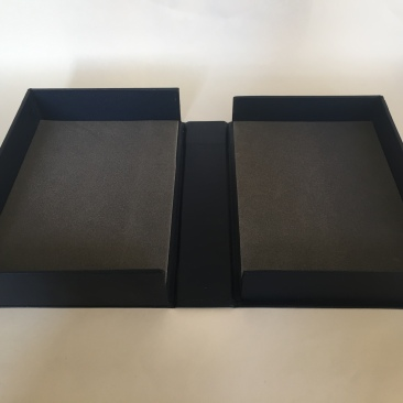 Image of a clamshell or drop spine box made from millboard and covered in blue bookcloth opened flat on a surface