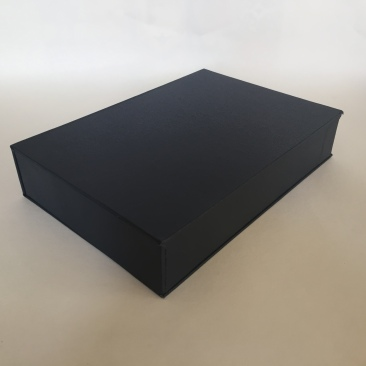 Image of a clamshell or drop spine box made from millboard and covered in blue bookcloth closed flat on a surface