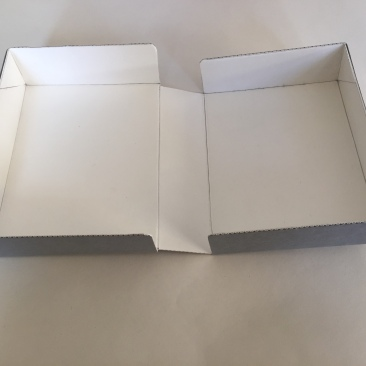 Image of a clamshell or drop spine box made from corrugated board opened flat on a surface