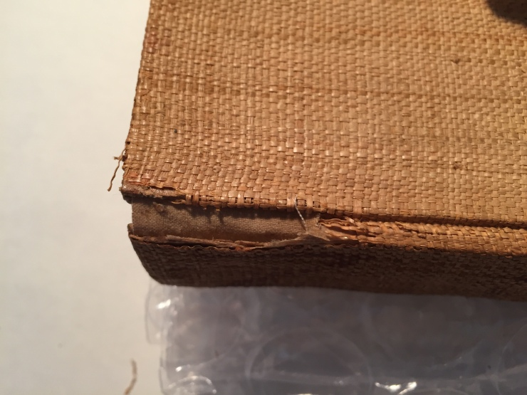 At the top of the spine a section of brown cloth in bridging a gap in the cover material.