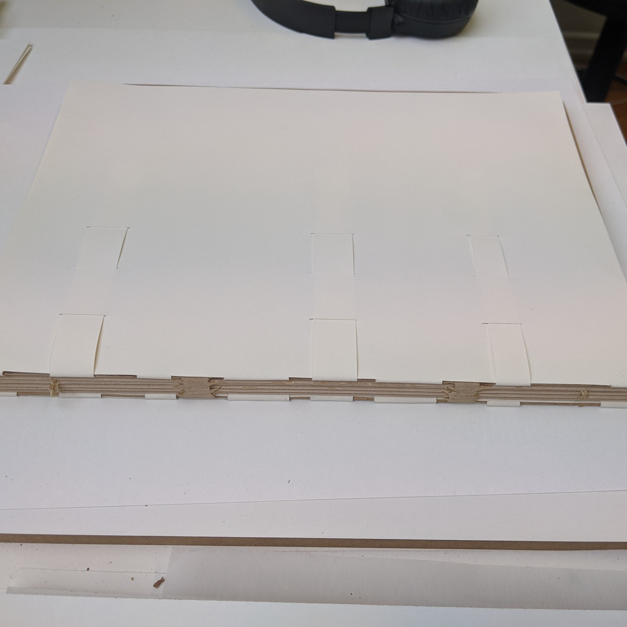 Image shows the construction of a wrapper which wraps around the board of the book around the spine edge. It is made up of two sheets of buffered archival paper which has tabs cut out that pass around the spine edge of the board to the other side of the board. Then the tabs are woven into slots in the corresponding wrapper.