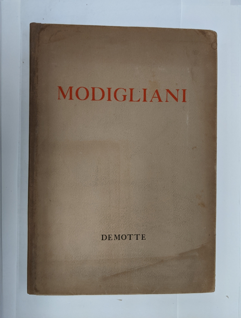 The front cover of the book is shown after treatment has been completed. The dust cover is a dark brown paper and the title 'Modigliani' is printed in red text across the front.