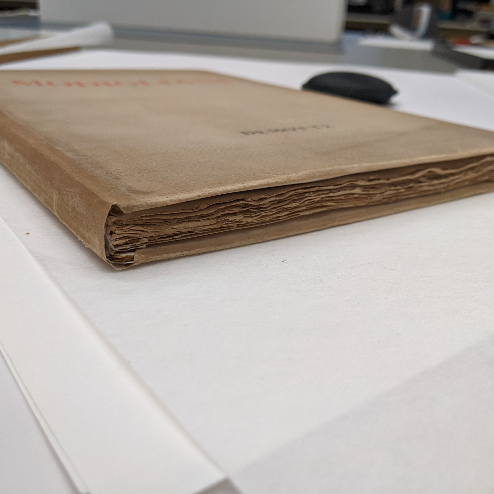 The image shows a view of the finished book from the bottom edge. You can see the rough cut edges of the books pages and the newly repaired dust jacket wrapped around the book.